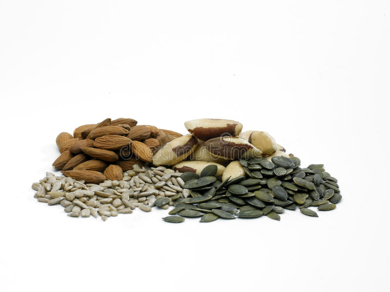Nuts and seeds. A selection of shelled nuts and seeds on a white background royalty free stock images