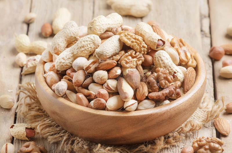 Nuts set assortment in bowl with almonds, pistachios, cashews, hazelnuts, peanuts, Brazil nuts, walnuts, vintage wooden kitchen stock photo
