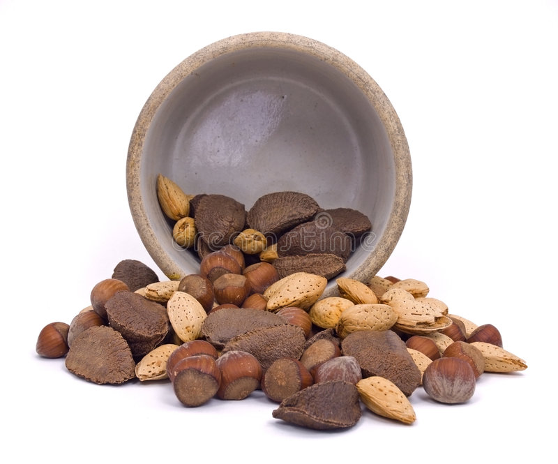 Nuts Spill Out of Crock. Mixed batch of nuts spill out of old crock on white background royalty free stock photo