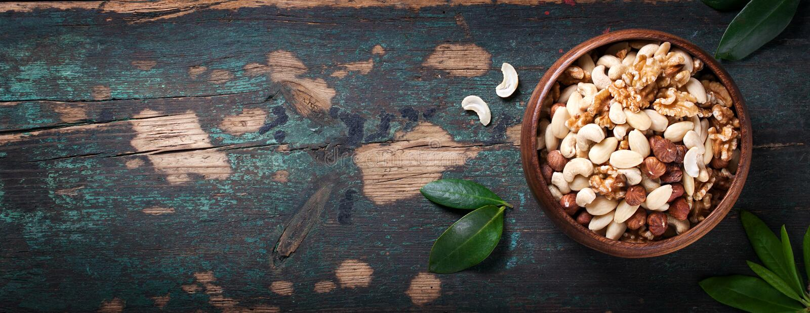 Nuts in vintage spoons on a vintage dark background royalty free stock photography