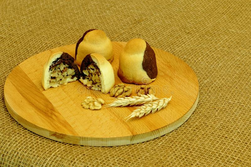 Delicious homemade shortbread cookies filled with walnuts, spikelets of wheat and nuts on round wooden board on rough homespun stock photos