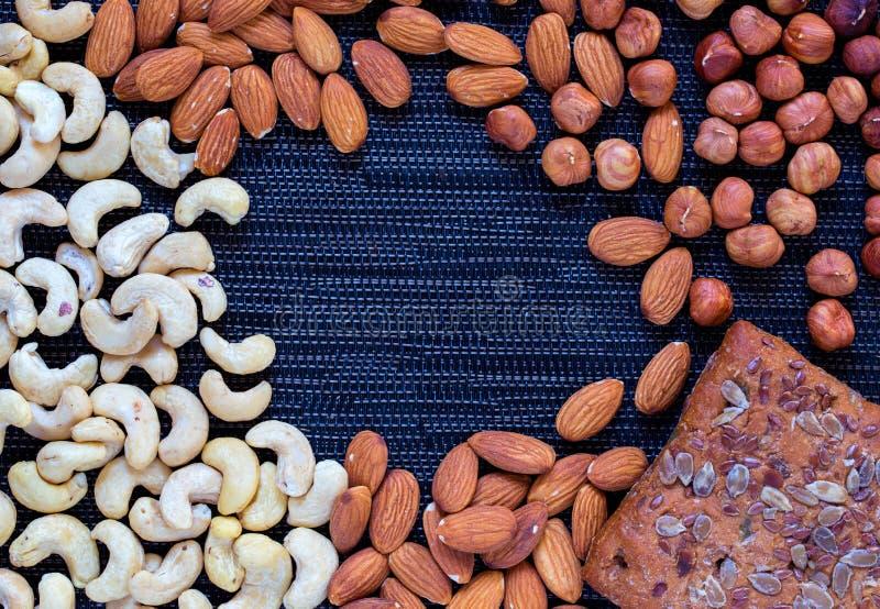 Nuts Zusammenstellung und Roggen säen Brotfotohintergrund Acajoubaum, Mandel, Haselnussmischungsnahaufnahme stockbild
