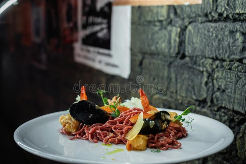 Nuttige bruine spaghetti met sappige calamari met mosselen met garnalen en greens op een plaat in een restaurant Heerlijke zeevru royalty-vrije stock afbeeldingen