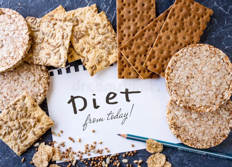 Nuttige dieet, knäckebrood, vlokken, boekweit, koekjes met zonnebloem op een geweven achtergrond Een blad van te schrijven potloo royalty-vrije stock afbeelding