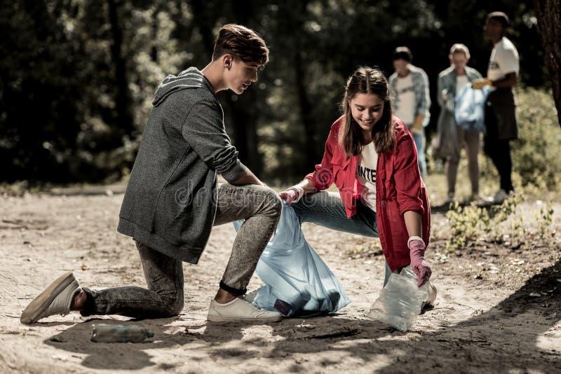 Nuttige donker-haired jongen die aan zijn vriend komen en haar schoonmakend afval in bos helpen stock afbeeldingen