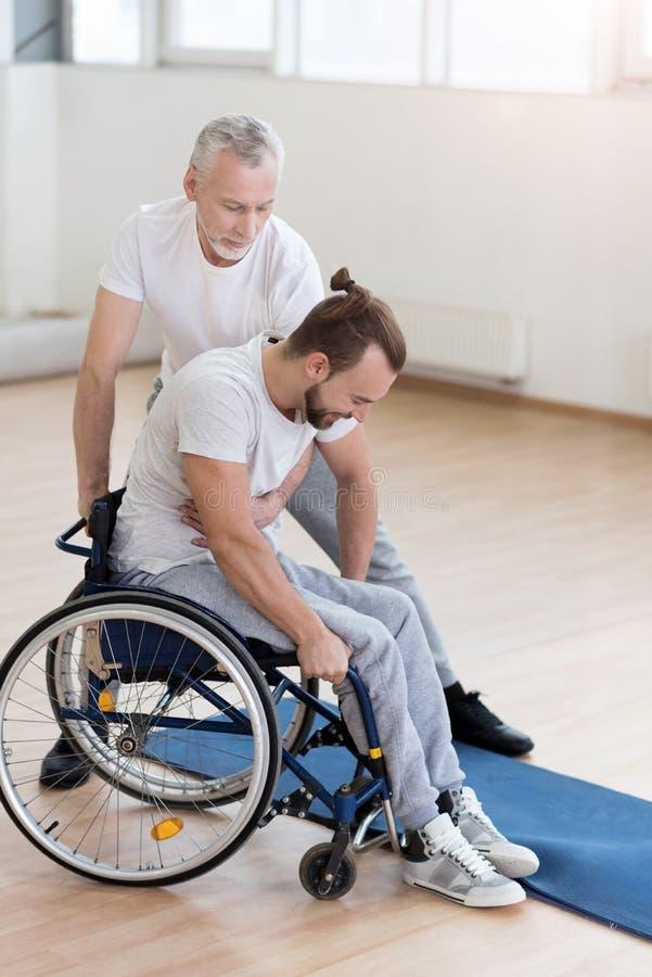 Nuttige gebaarde vader die zijn gehandicapte zoon in de gymnastiek helpen stock foto