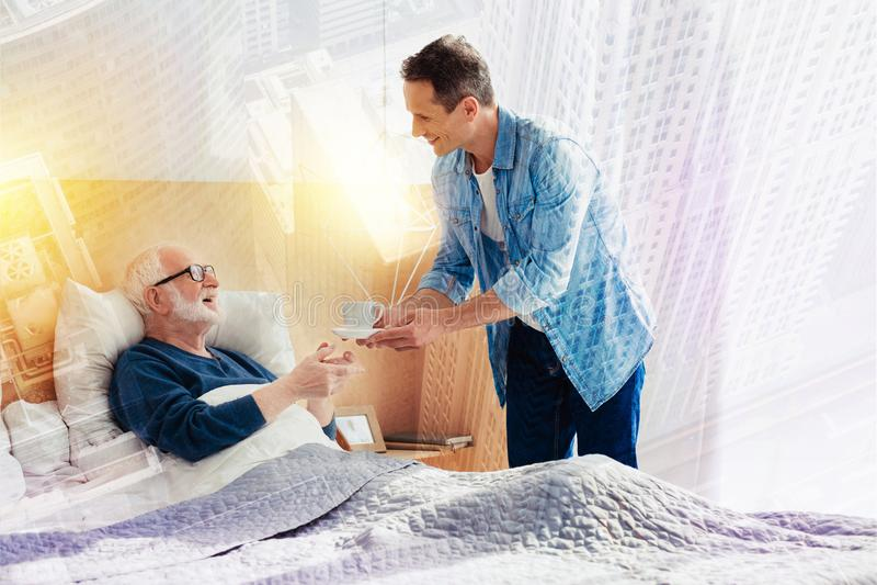 Nuttige jonge mens die koffie geven aan zijn het oude vader en glimlachen stock foto's