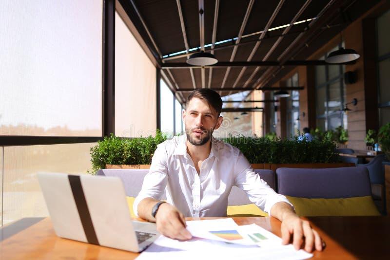 Nuttige manager die van koel resultaat genieten en met laptop bij t werken royalty-vrije stock foto's
