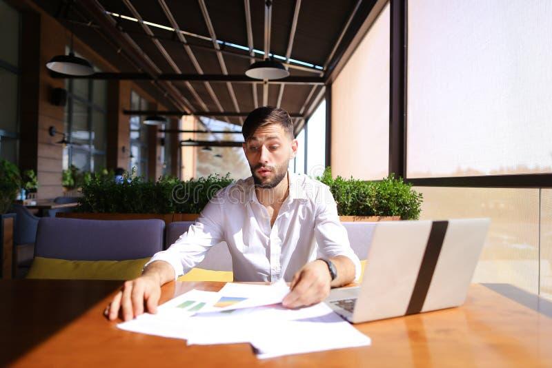 Nuttige manager die van koel resultaat genieten en met laptop bij t werken stock foto