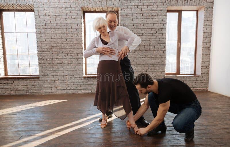 Nuttige rijpe dansinstructeur die verouderd paar in de balzaal onderwijzen royalty-vrije stock foto