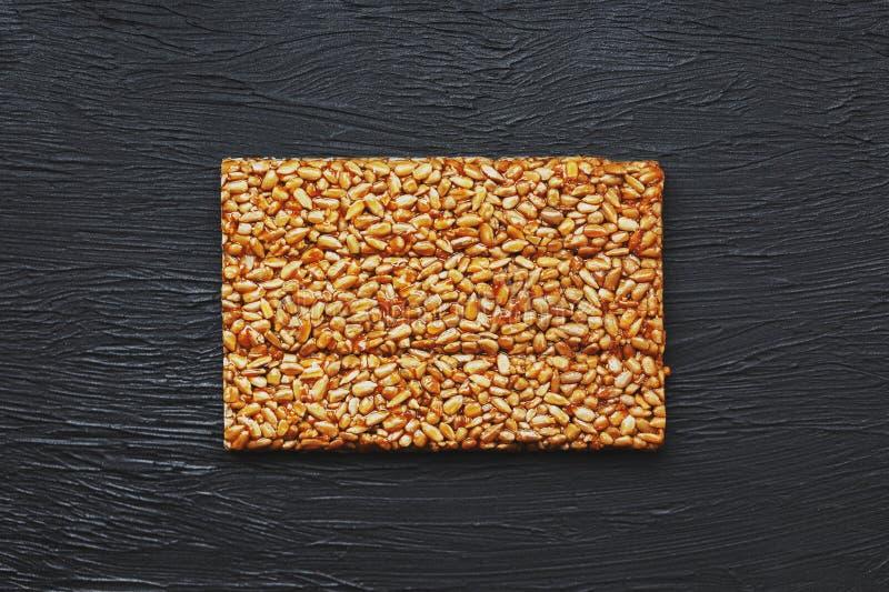Nuttige snacks Het Voedsel van het geschiktheidsdieet Boletchik van de zaden van de kozinakizonnebloem, energiebars Zwarte weefse stock fotografie