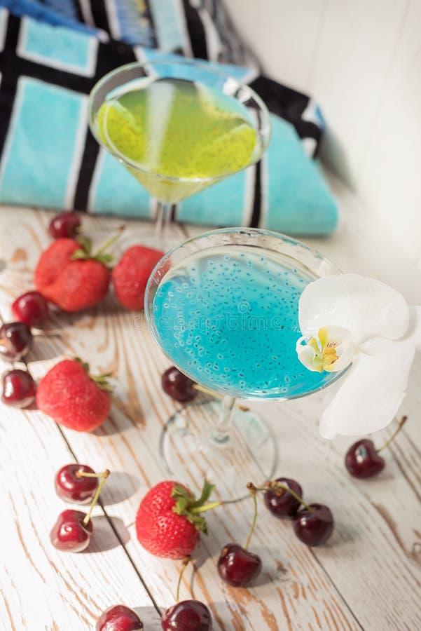 Nuttige verfrissende dranken met chia en basilicumzaden, fruit en strandhanddoek stock afbeelding
