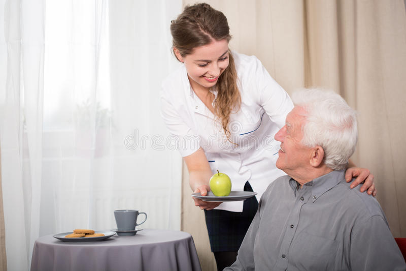 Nuttige verpleegster en glimlachende gepensioneerde stock afbeelding