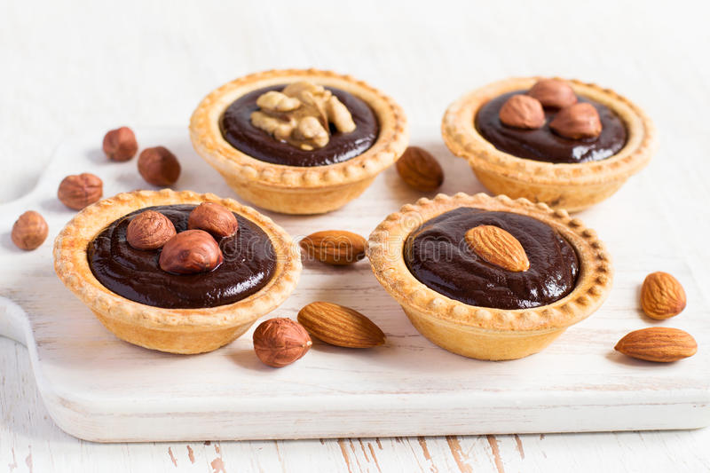 Nutty dessert - small tarts with different nuts and chocolate.  stock images