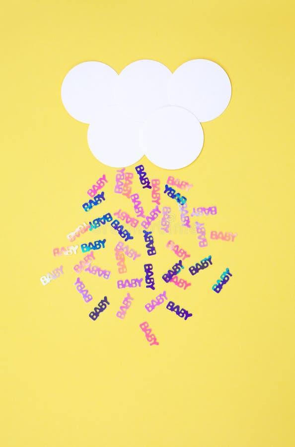 Nuvem branca no fundo amarelo com o bebê colorido pastel dos confetes fotografia de stock