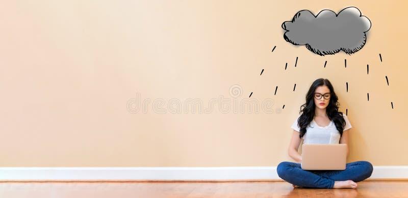 Nuvem de chuva com a mulher que usa um portátil imagens de stock royalty free