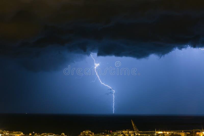 A nuvem maci?a para moer os parafusos de rel?mpago que batem o horizonte da cidade ilumina-se imagens de stock royalty free