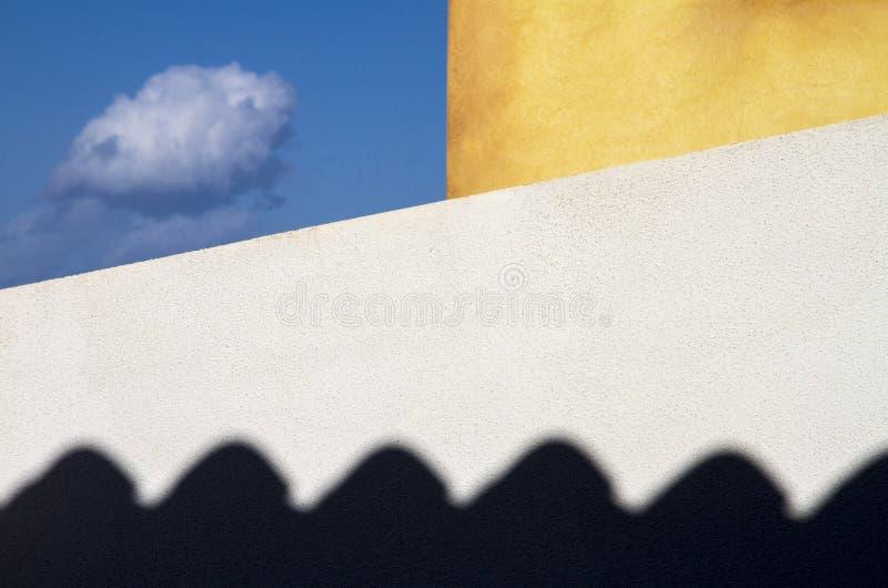 Nuvem prendida Duas paredes exteriores da casa, branco e amarelo, limite um a parte pequena de céu azul aonde uma nuvem pequena v imagem de stock royalty free