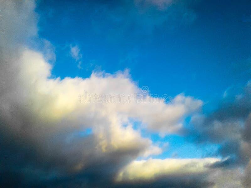 nuvens Amarelo-brancas em um céu azul fotografia de stock