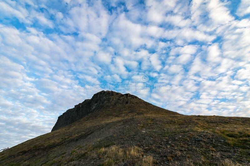 Nuvens bonitas acima de Platafjellet no verão Montes rochosos com alguma vegetação Foto tomada na meia-noite, cena fotografia de stock
