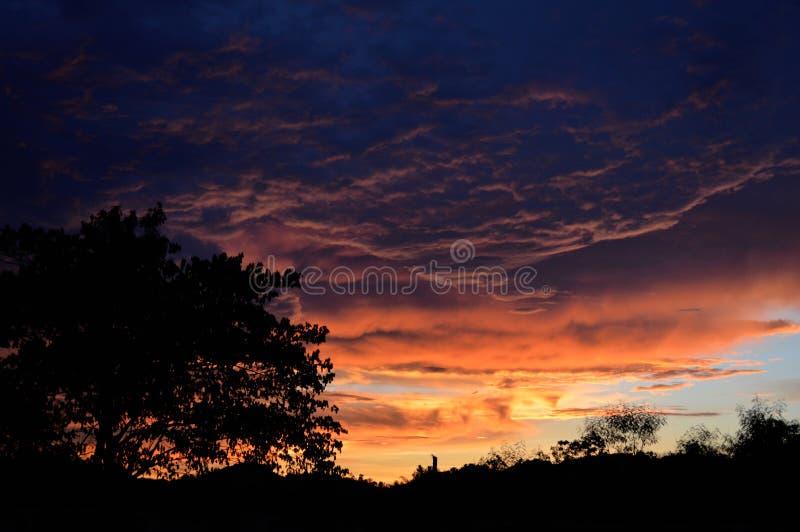 Nuvens bonitas do por do sol no céu alaranjado imagem de stock royalty free