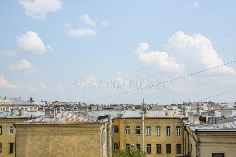 Nuvens bonitas e poderosas contra o céu azul e os telhados da cidade imagem de stock