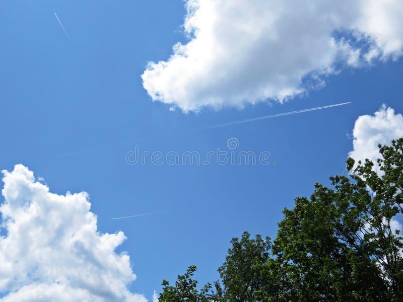 Nuvens brancas e pretas bonitas em um céu azul com luz solar no fundo com árvore fotografia de stock