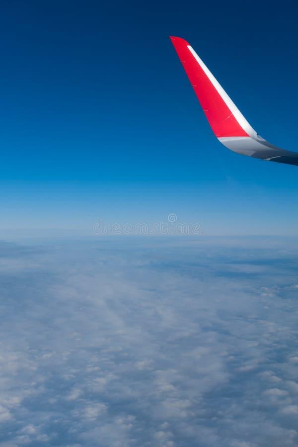 Nuvens, céu e asa como a janela completamente vista de um avião imagem de stock