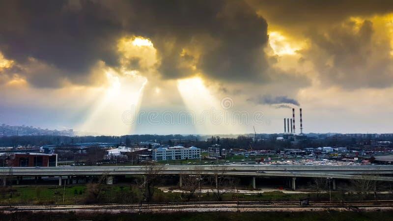 Nuvens chuvosas escuras pretas sobre a cidade densa urbana poluída com dois furos grandes nas nuvens imagens de stock royalty free