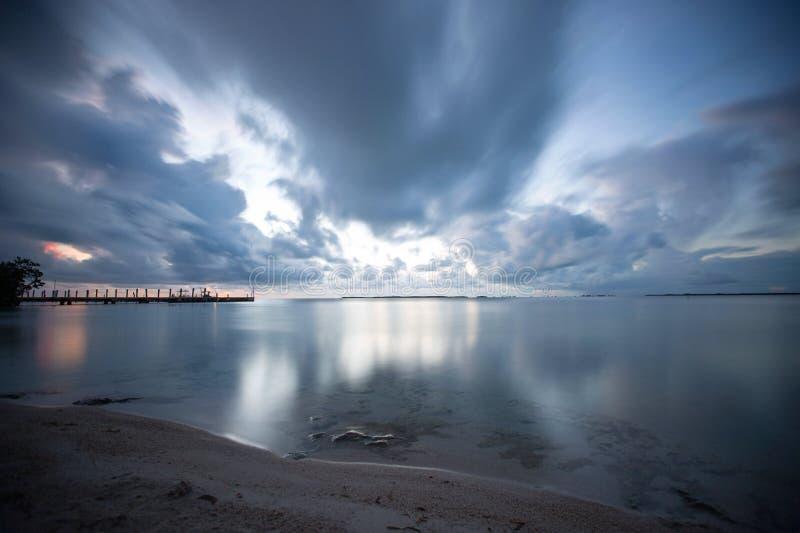 Nuvens cor-de-rosa e de prata que refletem no oceano imagens de stock