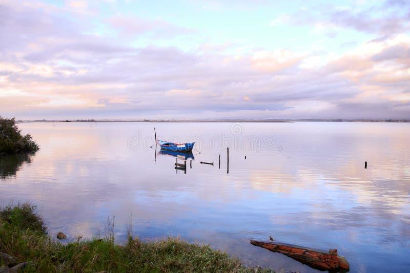 Nuvens cor-de-rosa e o barco azul na lagoa foto de stock royalty free
