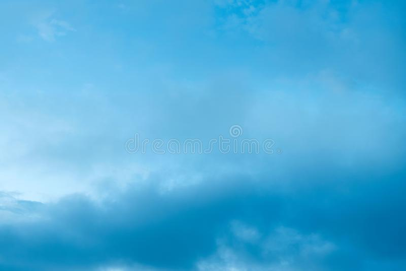 Nuvens de cúmulo do por do sol com o fundo borrado do céu azul do por do sol que defocusing imagens de stock