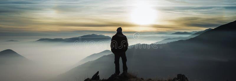 Nuvens de observação das montanhas do homem de um pico fotos de stock