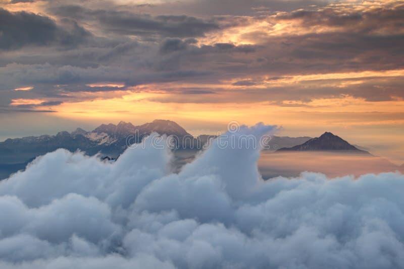 Nuvens de ondulação, picos irregulares e céu alaranjado acima da névoa da manhã imagens de stock royalty free