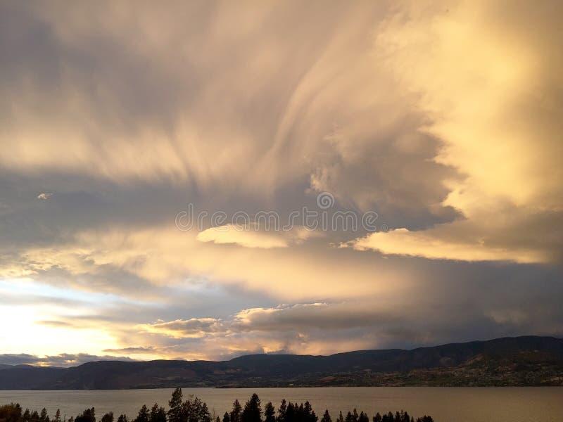 Nuvens de tempestade brilhantes sobre montanhas e lago no por do sol imagens de stock