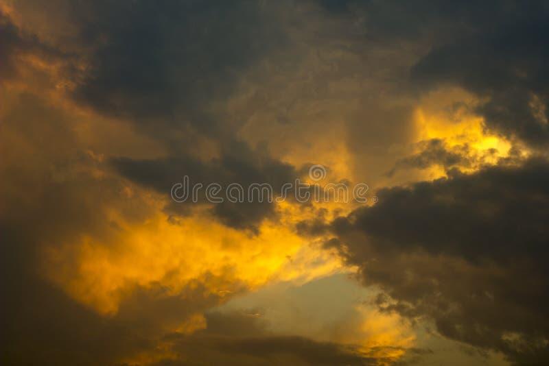 Nuvens de tempestade cinzentas alaranjadas brilhantes em um céu escuro do por do sol Nuvens de chuva no céu imagens de stock royalty free