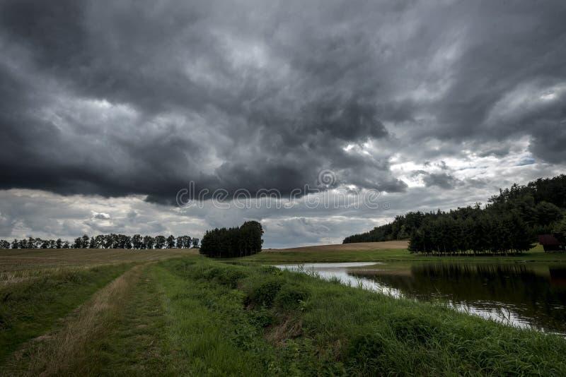 Nuvens de tempestade escuras acima de uma lagoa entre campos na floresta em Boêmia imagem de stock royalty free