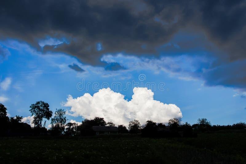 Nuvens de tempestade escuras sobre uma nuvem branca pequena Dur diferente das nuvens foto de stock royalty free