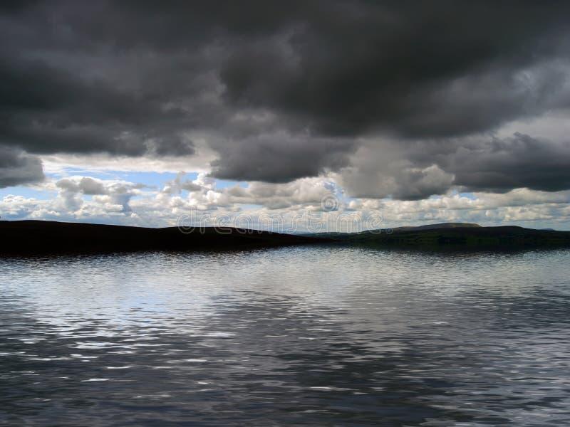 Nuvens de tempestade sobre a água ilustração royalty free