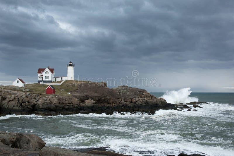 Nuvens de tempestade sobre o farol com deixar de funcionar das ondas imagens de stock royalty free