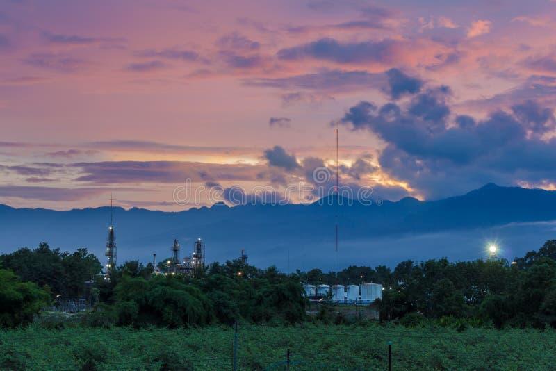 Nuvens do céu do por do sol de Swilight com plantas do petróleo foto de stock