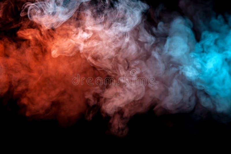 Nuvens do fumo colorido isolado: azul, vermelho, laranja, cor-de-rosa; enrolamento em um fundo preto na obscuridade foto de stock