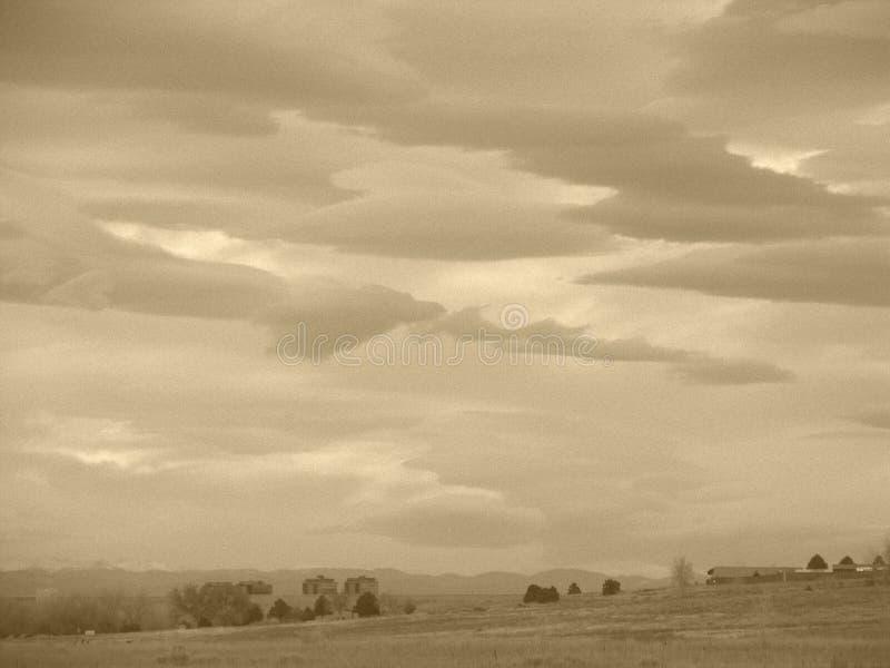 Nuvens do Sepia sobre o campo fotografia de stock