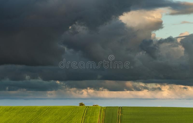 Nuvens dramáticas chuvosas sobre campos verdes no Reino Unido foto de stock royalty free