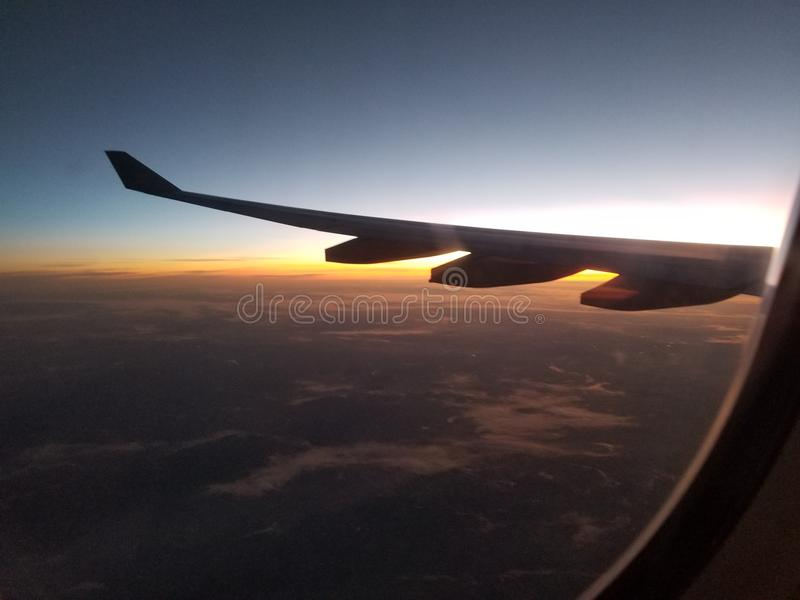 Nuvens e asa circunvizinha do avião do por do sol imagens de stock royalty free