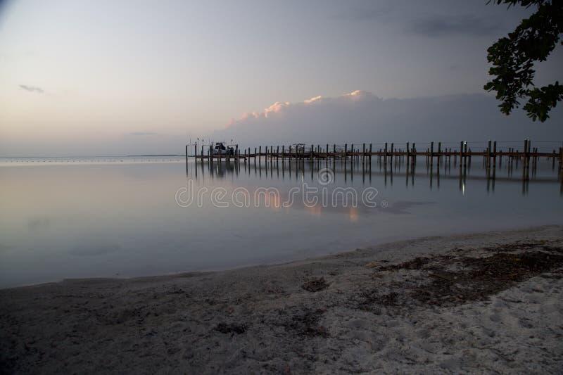 Nuvens e uma doca que reflete na água fotografia de stock royalty free