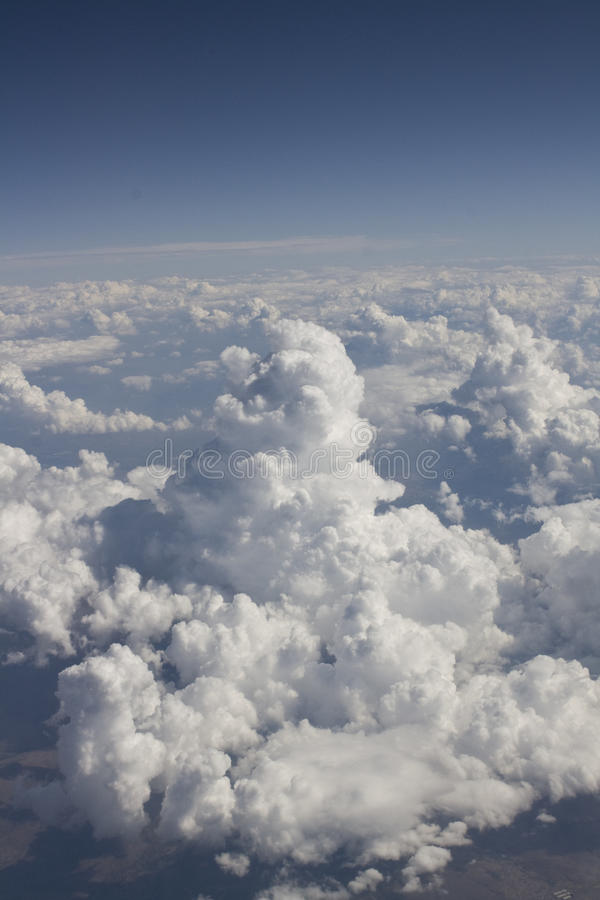 Nuvens elevadas acima no céu azul fotografia de stock