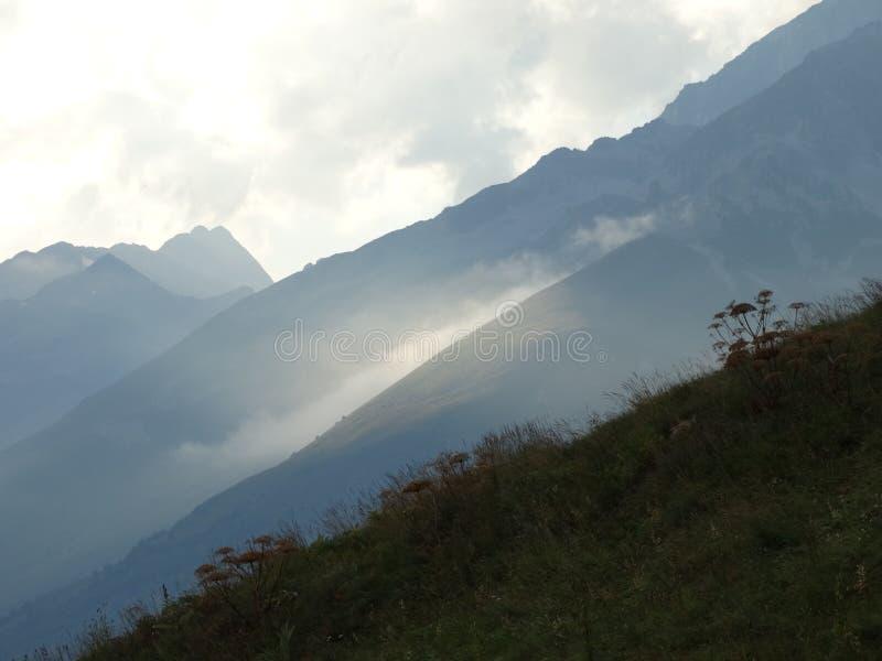 Nuvens em inclinações de montanha fotografia de stock