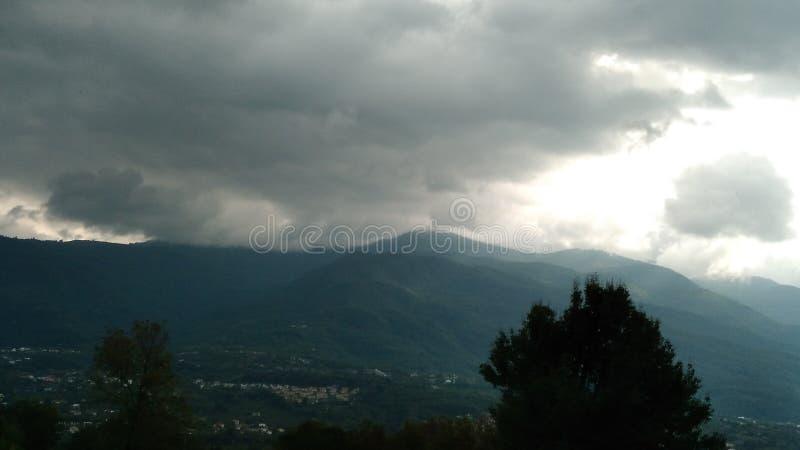 Nuvens escuras e a montanha fotos de stock