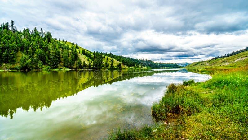 Nuvens escuras e montanhas circunvizinhas que refletem na superfície lisa da água do lago Trapp imagem de stock